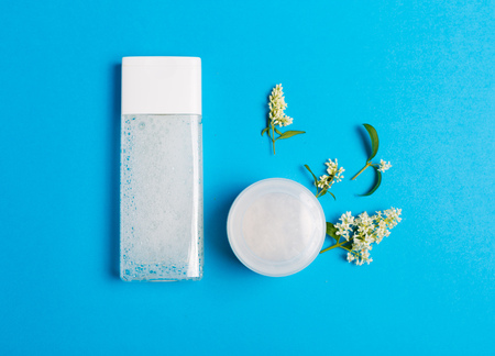 Set of cosmetics on a blue background with white petals