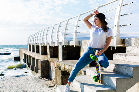 Beautiful yound woman with a skateboard on a beach Stock Photo