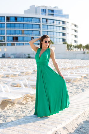Beautiful young woman in a green gown on the beach 写真素材 - 107492348