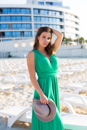 Beautiful young woman in a green gown on the beach 写真素材 - 107492352