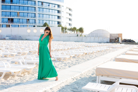 Beautiful young woman in a green gown on the beach 写真素材 - 107492389