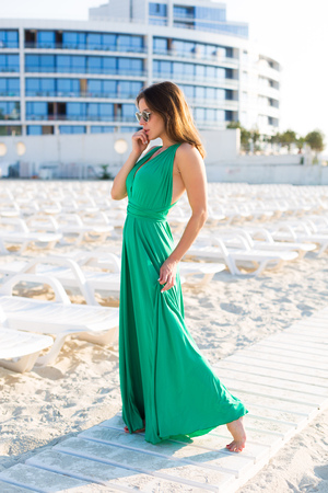 Beautiful young woman in a green gown on the beach