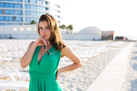 Beautiful young woman in a green gown on the beach 写真素材 - 107492396