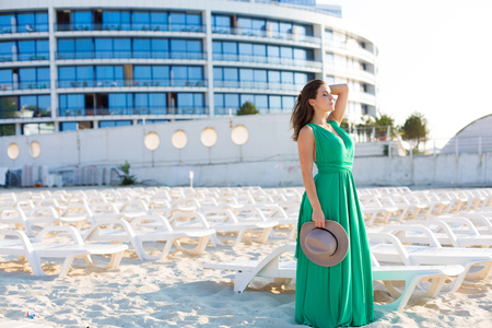 Beautiful young woman in a green gown on the beach 写真素材 - 107492401