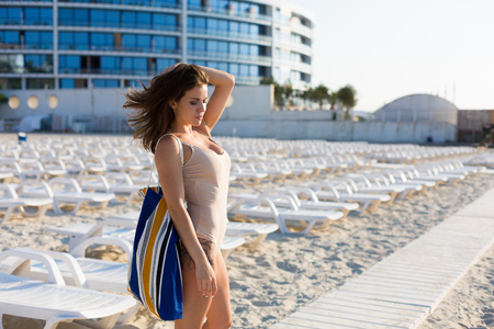 Woman wearing a nude swimsuit at the summer beach 写真素材 - 107492404