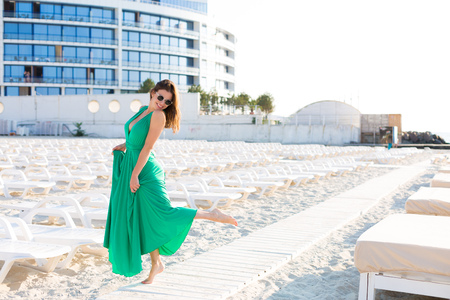 Beautiful young woman in a green gown on the beach 写真素材 - 107492408