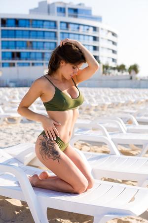 Beautiful woman wearing bikini and tanning on the beach