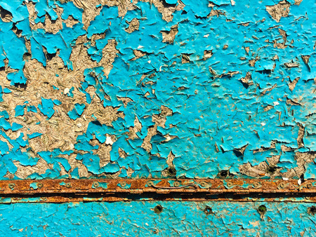 Blue wooden background with chipped paint and rust