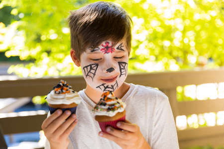 Boy with a face paint eating spooky Halloween cupcakes Stock Photo