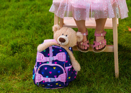 Cute kindergardener girl with a backpack and a teddy
