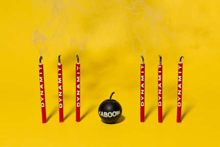 Red dynamite birthday candles blown out on a bright yellow background