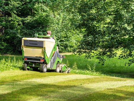 Lawn mowing with lawn tractor in the park
