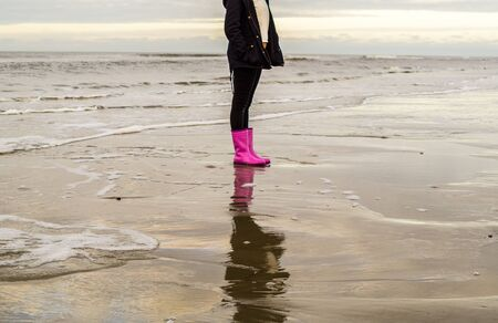 Girl is running with rubber boots at the beach Stock Photo