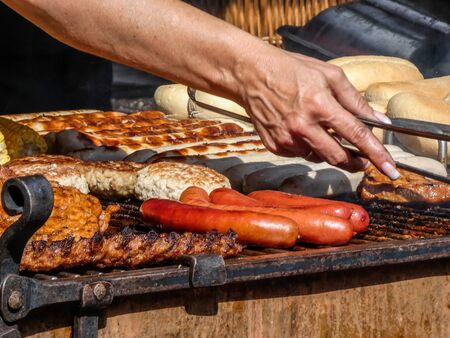 Barbecue: Woman prepares sausages and steaks Banco de Imagens