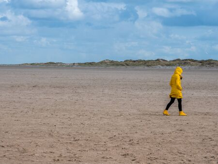 Woman in yellow raincoat at the North Sea Stockfoto - 131094625