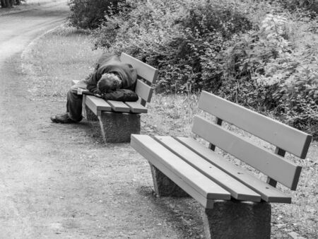 Man is sleeping on a park bench in Germany