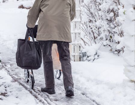 Pensioner in winter with a rollator