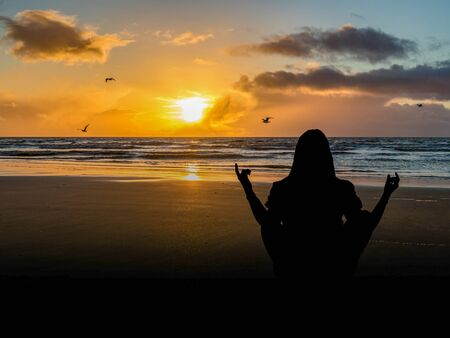 Silhouette on meditates at the sea