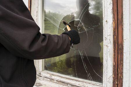 Burglar entering to house trough window Stock fotó