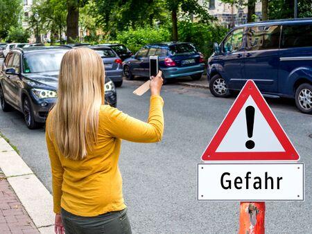 Frau überquert die Straße mit Handygefahr Deutsch Standard-Bild