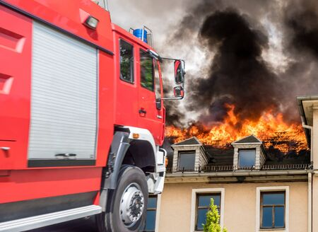 Fire service with burning house Stok Fotoğraf