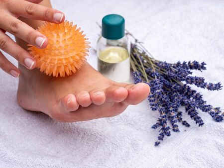 Foot reflexology massage with massage ball in a practice