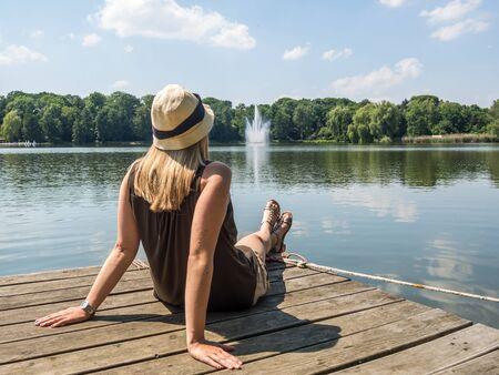 woman sitting on plattform at the waterside