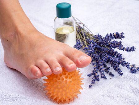 Fußreflexzonenmassage mit Massageball in einer Praxis