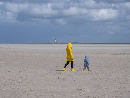 Woman is walking with her child on the beach at the North Sea