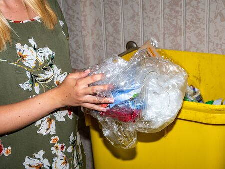Woman throws away plastic into the barrel