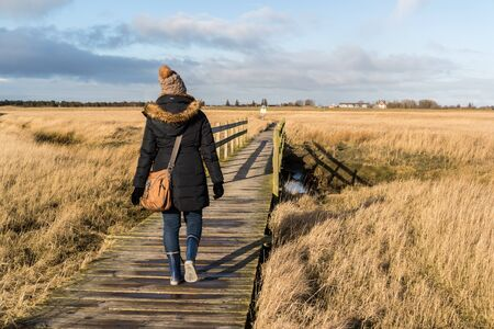 Woman running in winter on the beach path at the North Sea