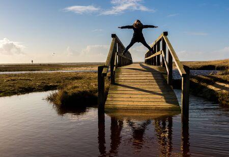 Woman is standing on wooden bridge