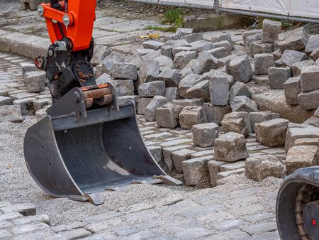 Road construction paving stones gardening with an excavator