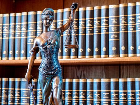 law figure justice statue in lawyers office with bookshelf