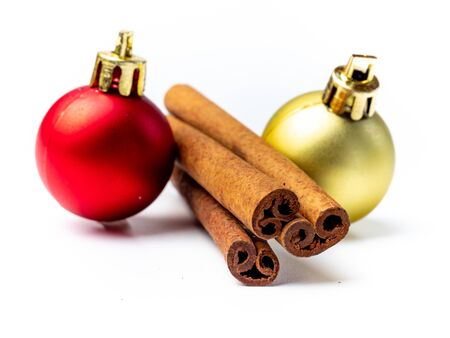 Cinnamon sticks and Christmas baubles isolated Фото со стока