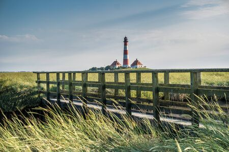 Wooden bridge at Westerhever lighthouse in Germany Stock Photo