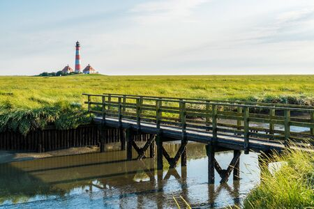Salt marshes with wooden bridge at Westerhever lighthouse Stock Photo