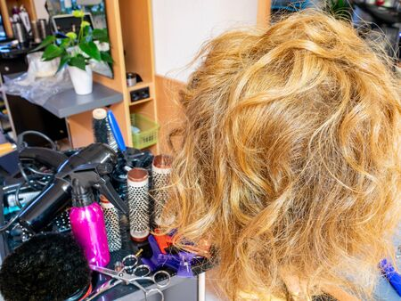 blonde woman gets curls at the hairdresser