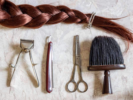 Tool in hairdressing craft vintage with red hair braid