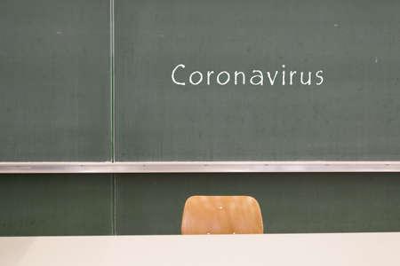 Coronavirus is written on a blackboard in the school in german