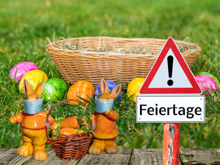 Holidays warning sign with Easter bunny and basket in German 免版税图像