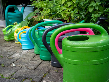 colorful watering cans at the garden 免版税图像