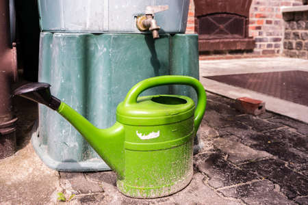 green watering can with water tank in the garden