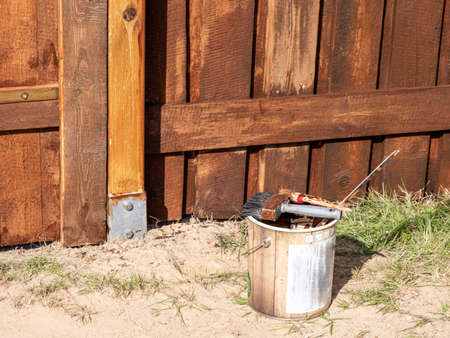 Paint buckets with paint on a wooden fence Standard-Bild