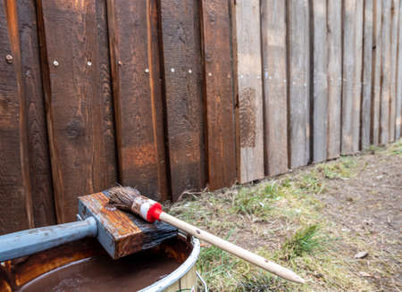Paint bucket with brush on a wooden fence
