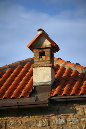 Pipe and tiled roof, day. Stock Photo