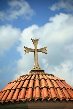 Cross at tiled dome, day. Stock Photo