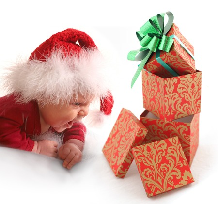 Baby in red hat looking at Christmas gift Stock Photo