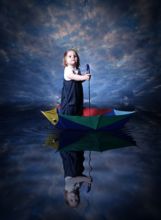 Little girl is sailing on the sea using the umbrella as a ship