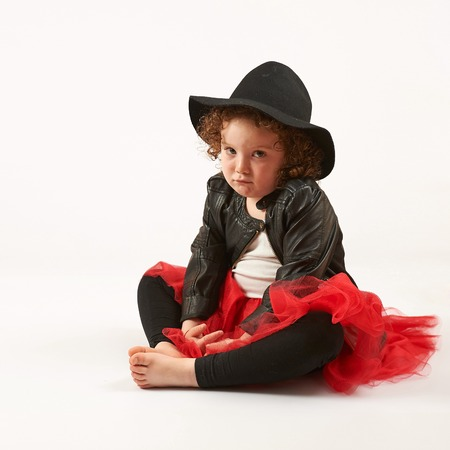 pouting: Little girl with black hat sitting and pouting Stock Photo